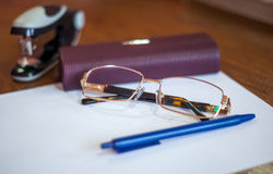 Ballpoint pen on a sheet and reading glasses with box Royalty Free Stock Images