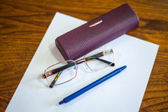 Ballpoint pen on a sheet and reading glasses with box Royalty Free Stock Image