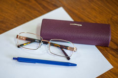 Ballpoint pen on a sheet and reading glasses with box Royalty Free Stock Photos