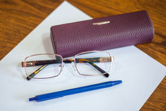 Ballpoint pen on a sheet and reading glasses with box Stock Photos