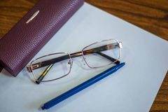 Ballpoint pen on a sheet and reading glasses with box Stock Image