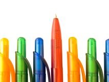 Ballpoint pens. Red pen in the row of the multicolored ballpoint pens royalty free stock photography