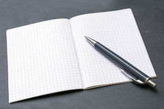 Ballpoint pens and a blank notebook with graph paper Royalty Free Stock Photo