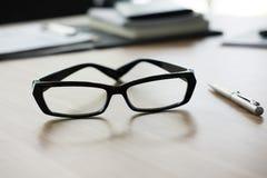 ballpoint pióro, eyeglasses, notatnik na biurowym biurku biznes, wo Zdjęcie Royalty Free
