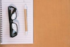 ballpoint pióro, pusty notatnik, eyeglasses na biurowym biurku Busine Zdjęcie Royalty Free
