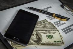 Ballpoint pióro z wiązką dolary i telefon komórkowy obraz royalty free