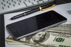 Ballpoint pióro z wiązką dolary i telefon komórkowy zdjęcia royalty free