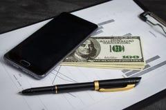 Ballpoint pióro z wiązką dolary i telefon komórkowy obraz stock
