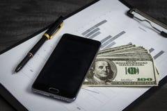 Ballpoint pióro z wiązką dolary i telefon komórkowy obrazy royalty free
