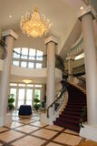 Ballroom Staircase. Elegant building entrance with circular staircase, crystal chandelier, marble floors, and red carpet Stock Photography