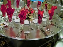 Ballroom table setting with spandex table cover, red centerpiece and red napkins. Banquet table setting with red theme on silver spandex in Hawaii resort Stock Image