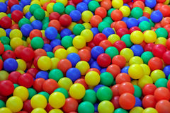 Balls. Background of lots of colorful plastic balls in red, yellow, green and blue for kids to play with on the playground outdoors Stock Image