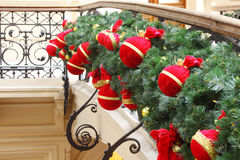Balls, bags, toys on artificial branch of fir-tree. Red miniature balls, bags, toys on artificial branch of fir-tree on handrails, indoor royalty free stock images