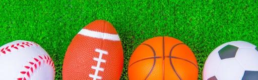 Balls for baseball, american football, basketball, soccer. lie on the green. Outdoor sports championship.