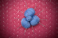 Balls blue yarn are on the pink knitwear Stock Photo