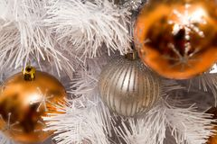Balls on branches. Close-up of toy balls hanging on white fluffy branch of artificial fir tree Stock Photo