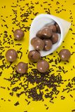 Balls and chocolate chips. On a white cone over a yellow background Royalty Free Stock Image