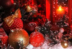Balls and Christmas bell are covered with snow in the light of a red lantern on the background of New Year`s scenery. The magic of Christmas and New Year Royalty Free Stock Images
