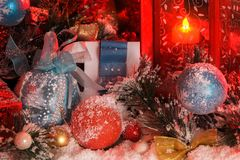 Balls and Christmas bell are covered with snow in the light of a red lantern on the background of New Year`s scenery. The magic of Christmas and New Year Stock Photos