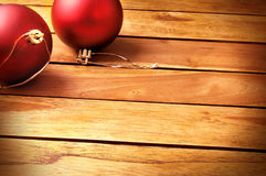 Balls Christmas decoration on a table wooden slats top diagonal. Red Christmas decoration with two red balls on a table wooden slats. Top and diagonal view stock photos