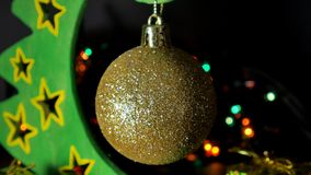 New Year`s yellow toy on an artificial Christmas tree, flashing light. Balls on the Christmas tree. Christmas background stock video footage