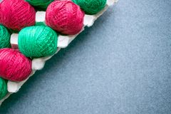 Balls of colored red and green yarn in a paper egg tray. Diagonal frame. Copy space. Skeins of cotton yarn for knitting and stock images