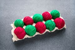 Balls of colored red and green yarn in a paper egg tray. Skeins stock image