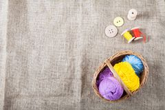 Colored threads and wooden buttons and a wicker basket are on sackcloth in the corner of the frame. Balls of colored threads and wooden buttons and a wicker royalty free stock image