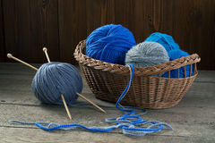 Balls of colored yarn in a basket on a wooden table Stock Image