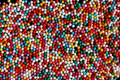 Texture multicolored bright little balls lie on a flat surface. Balls, colorful, color, background, many, coloured, white, texture, green, pattern, decoration stock photography