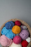 Balls of Colour Wool in Bowl on Grey Background Royalty Free Stock Images