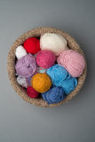 Balls of Colour Wool in Crocheted Bowl on Grey Background Royalty Free Stock Photos