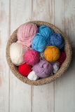 Balls of Colour Wool in Crocheted Bowl on Wooden Surface Royalty Free Stock Photos