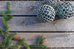 Balls in a fishing net on a wooden background with a spruce branch and cones.  Stock Photos