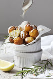 Balls of fried potatoes with lemon, rosemary and dripping yogurt sauce Stock Photo
