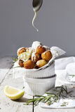 Balls of fried potatoes with lemon, rosemary and dripping yogurt sauce Royalty Free Stock Photo