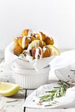 Balls of fried potatoes on little bowl with lemon, rosemary and dripping yogurt sauce Stock Photo