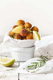 Balls of fried potatoes on little bowl with lemon slice and rosemary Stock Images
