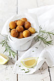 Balls of fried potatoes on little bowl with lemon slice and rosemary Royalty Free Stock Photography