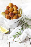 Balls of fried potatoes on little bowl with lemon slice and rosemary Royalty Free Stock Images