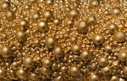 Balls of golden color of different size closeup. Bright gold shiny background. royalty free stock images