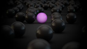 Balls invasion. A unique pink ball stays alone between black balls Royalty Free Stock Photo