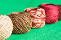 Balls of a multi-colored yarn on a green background Royalty Free Stock Photography