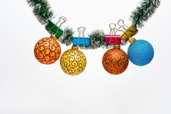 Balls with ornaments hang on shimmering green tinsel. Tinsel with pinned christmas ornaments, white background, copy. Space. Christmas ornaments concept royalty free stock photography