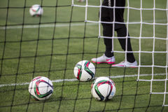 Balls of Paok team on the field of the stadium behind net during Royalty Free Stock Images