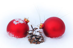 Balls, pine cone and dry grass in the snow Royalty Free Stock Photos