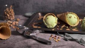 Pistachio ice cream in waffle cones. Balls of pistachio ice cream in waffle cones on a dark background stock footage