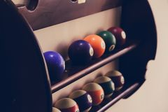 Balls for pool billiards on the shelf, billiard balls for American billiards colored on a wooden background. Close-up photo Royalty Free Stock Photos