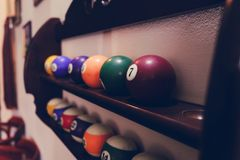 Balls for pool billiards on the shelf colored or white balls for billiards on a wooden background. Close-up photo. Soft focus Royalty Free Stock Photography