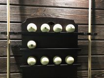 Balls for pool billiards on the shelf with cues from both sides royalty free stock image